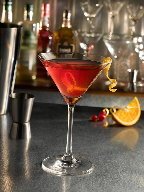 Cocktail cosmopolitan dans un verre à pied avec des zestes de citron