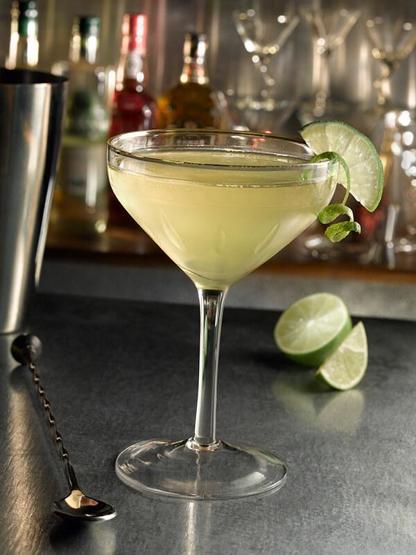 Cocktail daiquiri dans un verre à pied avec des zestes et quarts de citron vert