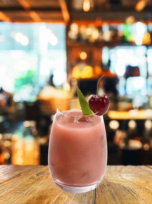 Cocktail dry pussy foot dans un verre avec des glaçons, feuille d'aloe vera et cerise