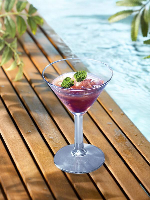Cocktail fraise exotique dans un verre à pied avec de la glace pilée avec des feuilles de menthe