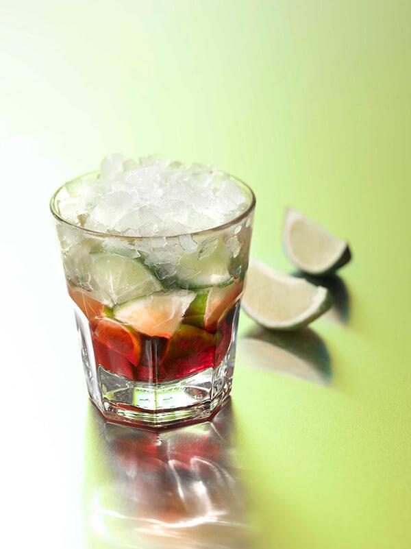 Cocktail lurrant tina dans un verre avec de la glace pilée et des morceaux de citron vert