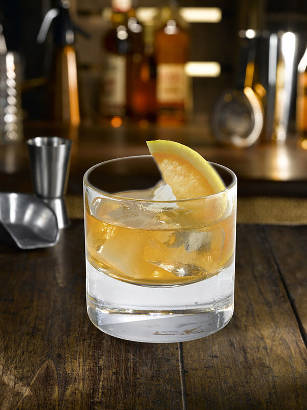 Cocktail le cap horn dans un verre avec des glaçons et des quarts de citron