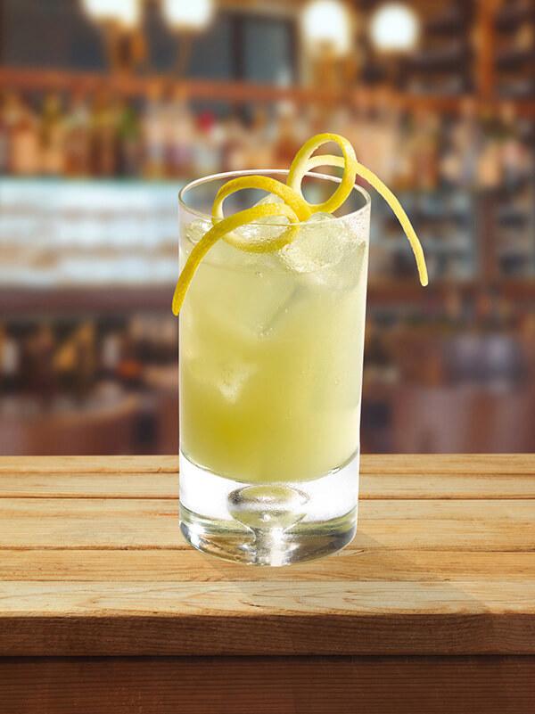 Cocktail lemon squash dans un verre avec des glaçons et des zestes de citron