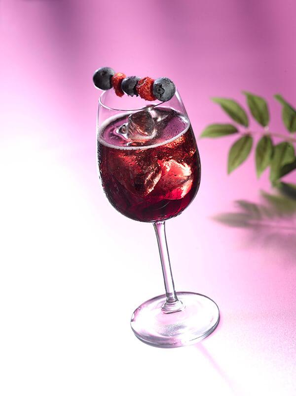 Cocktail mêlé cassis dans un verre à pied avec des glaçons et une brochette de fraise des bois et myrtille