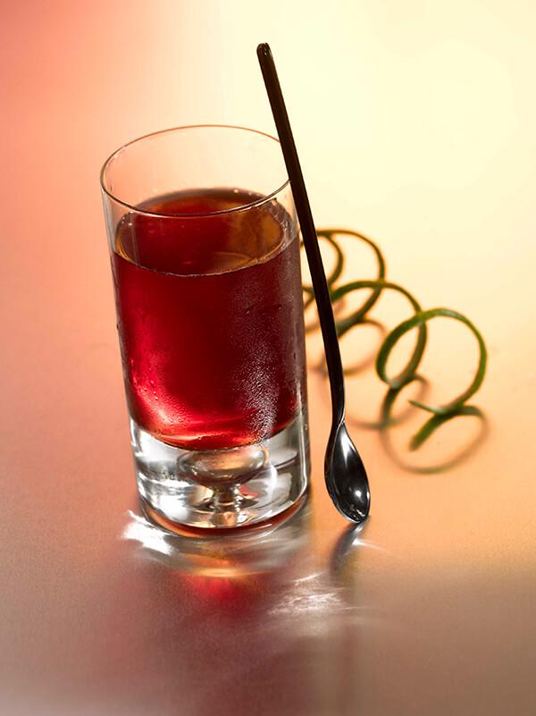 Cocktail murmure et chuchotement dans un verre avec zeste de citron vert et cuillère