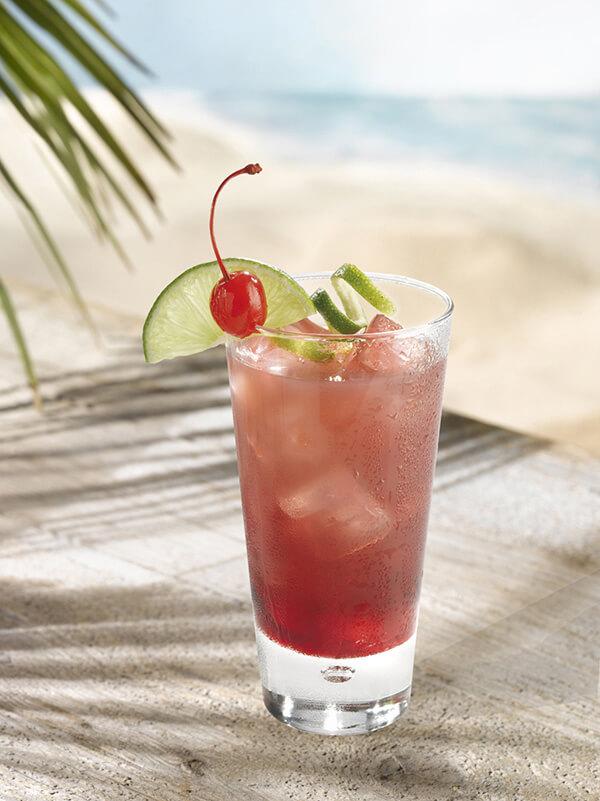 Cocktail orlando dans un verre avec des glaçons, zestes de citron vert, tranche de citron vert et cerise entière