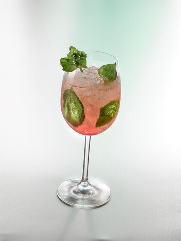 Cocktail parfum gourmand dans un verre à pied avec de la glace pilée, feuilles de menthe et de basilic
