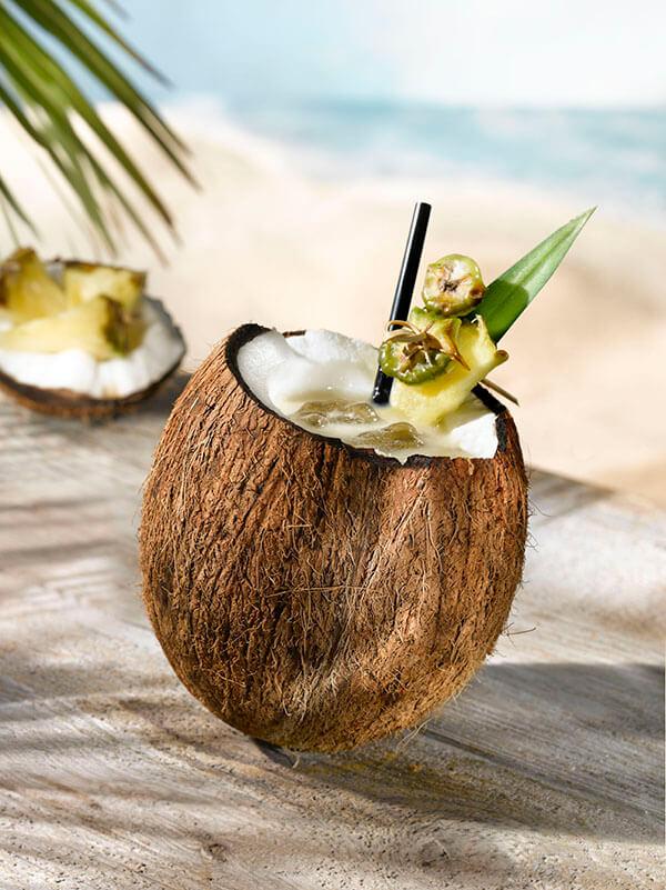 Cocktail pina colada dans une noix de coco avec fruits