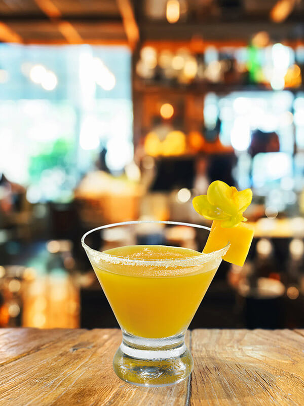 Cocktail pure brazilian dans un verre avec de la glace pilée, morceau de mangue et fleur de sureau