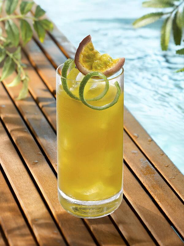 Cocktail so good sir dans un verre avec zeste de citron vert et morceau de fruit de la passion
