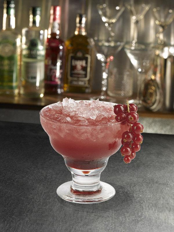 Cocktail soleil levant dans un verre à pied avec de la glace pilée et une grappe de groseille