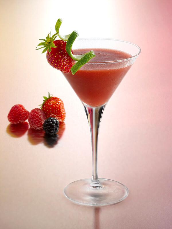 Cocktail strawberry daïquiri dans un verre à pied avec des zestes de citron vert et des fruits rouges