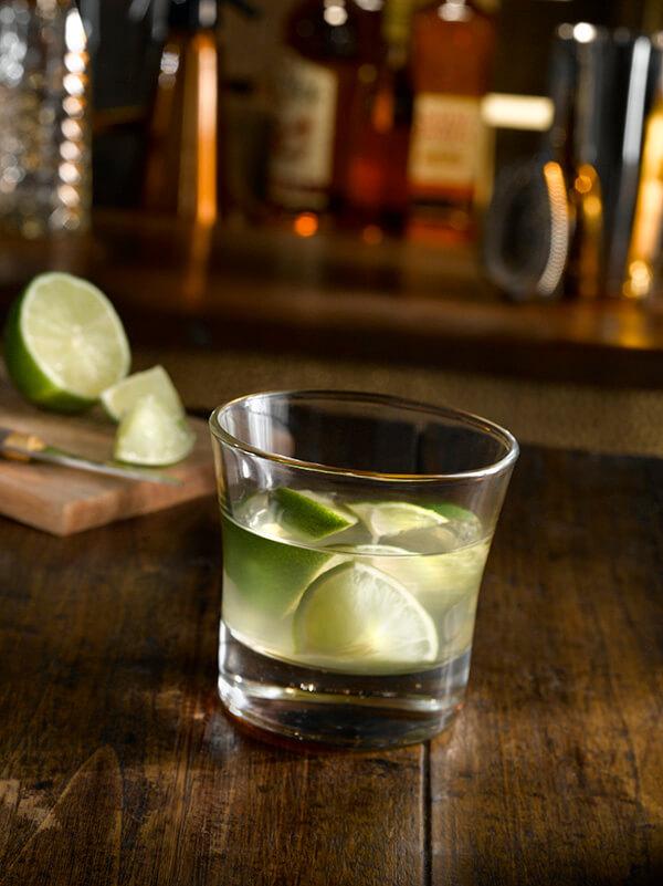 Cocktail ti punch dans un verre plat avec morceaux de citron vert