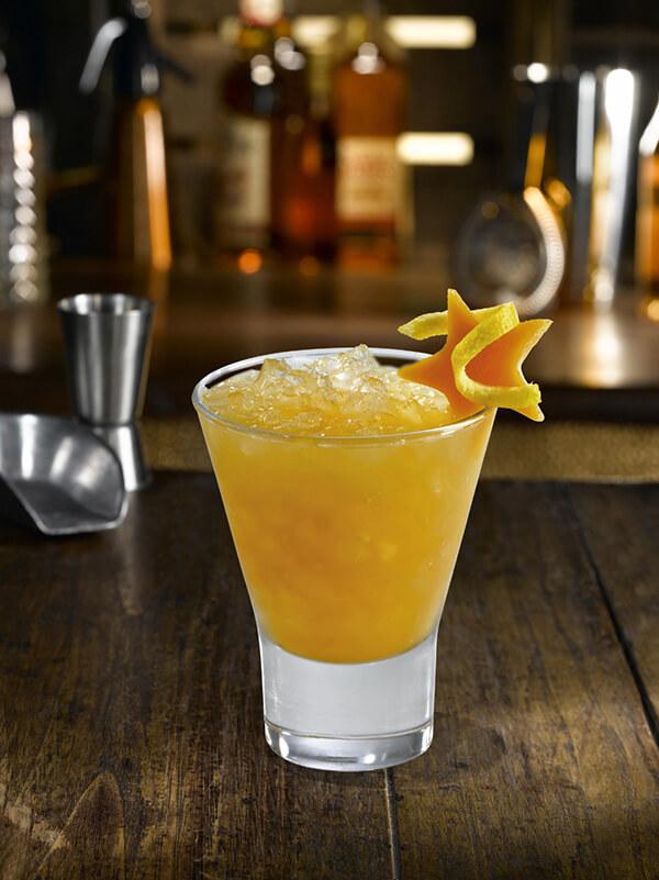 Cocktail tit yole dans un verre avec de la glace pilée, une tranche de carambole et un zeste de citron
