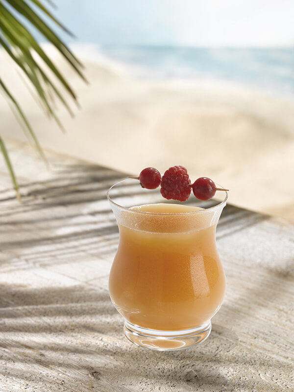 Cocktail vaudoo fever dans un verre avec de la glace et une brochette de groseille et framboise