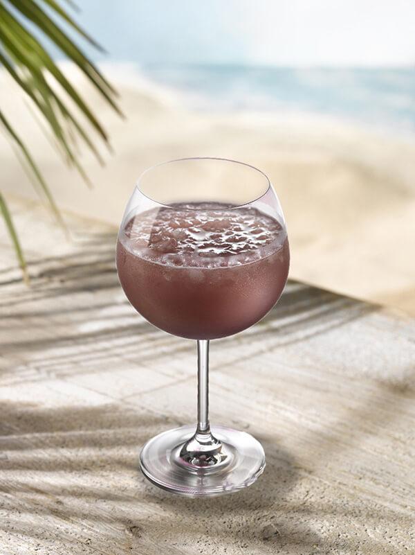 Cocktail violine dans un verre à pied avec de la glace pilée
