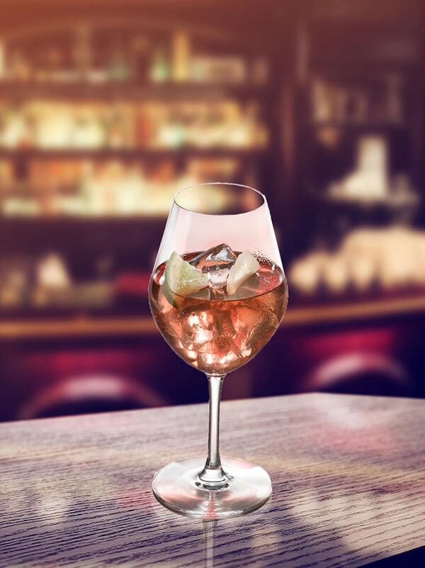Cocktail wine caipi dans un verre à pied avec des glaçons et des morceaux de citron vert