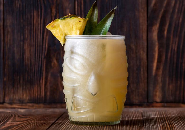 Cocktail tiki dans un verre sculptée avec visage traditionnel tiki et tranche d'ananas